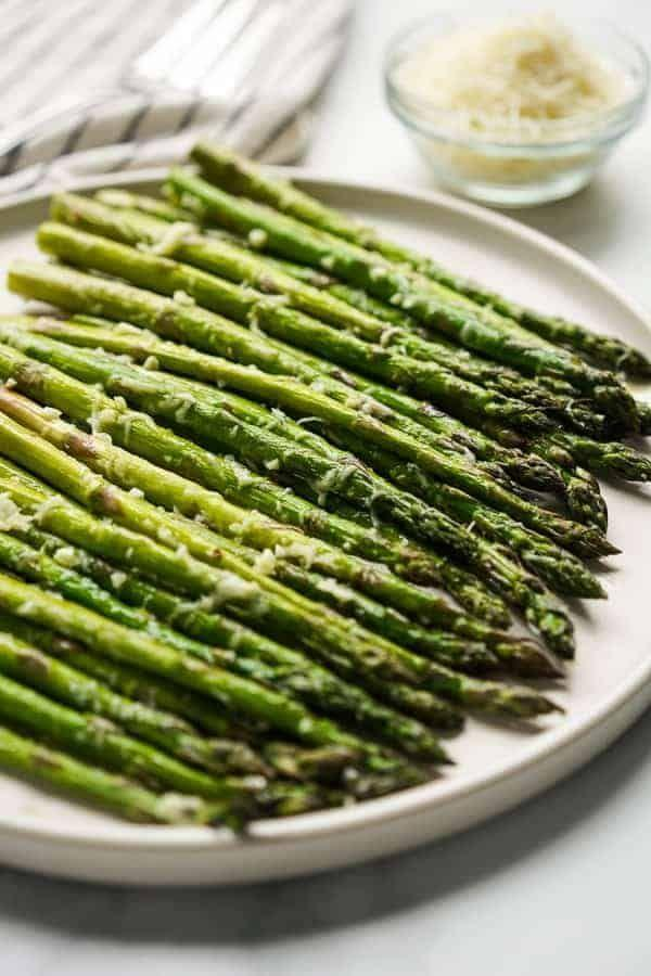 """<p>This simple take on asparagus couldn't be easier: You only need five ingredients and about 30 minutes to get it on the table.</p><p><strong>Get the recipe at <a href=""""https://www.joyousapron.com/easy-garlic-parmesan-asparagus/"""" rel=""""nofollow noopener"""" target=""""_blank"""" data-ylk=""""slk:Joyous Apron."""" class=""""link rapid-noclick-resp"""">Joyous Apron.</a></strong></p><p><a class=""""link rapid-noclick-resp"""" href=""""https://go.redirectingat.com?id=74968X1596630&url=https%3A%2F%2Fwww.walmart.com%2Fsearch%2F%3Fquery%3Dpioneer%2Bwoman%2Bcutting%2Bboard&sref=https%3A%2F%2Fwww.thepioneerwoman.com%2Ffood-cooking%2Fmeals-menus%2Fg35514088%2Fbest-side-dishes-for-ham%2F"""" rel=""""nofollow noopener"""" target=""""_blank"""" data-ylk=""""slk:SHOP CUTTING BOARDS"""">SHOP CUTTING BOARDS</a></p>"""