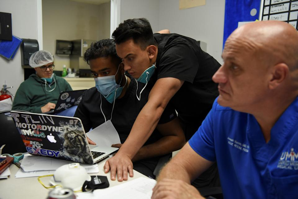 """Sanathan Aiyadurai, 27, and Diego Montelongo, 27, who are medical students, review a COVID-19 patient's status during a daily meeting lead by Dr. Joseph Varon, 58, the chief medical officer at United Memorial Medical Center (UMMC), during the coronavirus disease (COVID-19) outbreak, at UMMC in Houston, Texas, U.S., July 10, 2020.  REUTERS/Callaghan O'Hare     SEARCH """"COVID-19 HOUSTON VARON"""" FOR THIS STORY. SEARCH """"WIDER IMAGE"""" FOR ALL STORIES."""