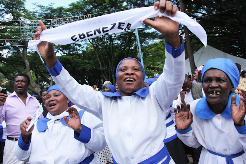 Members of the Anglican Church under the Bishop of Harare, Chad Gandiya, sing and dance in Africa Unity Square during a church service and cleansing ceremony of the church in Harare, Sunday, Dec. 16, 2012, following a court ruling which he won against his rival, excommunicated Bishop Nolbert Kunonga, who forcibly took over church buildings, orphanages, mission schools and hospitals resulting in the court challenge. (AP Photo/Tsvangirayi Mukwazhi)