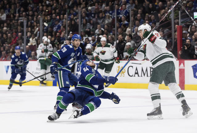 Minnesota Wild's Carson Soucy, right, checks Vancouver Canucks' Tyler Motte during the second period of an NHL hockey game Wednesday, Feb. 19, 2020, in Vancouver, British Columbia. (Darryl Dyck/The Canadian Press via AP)