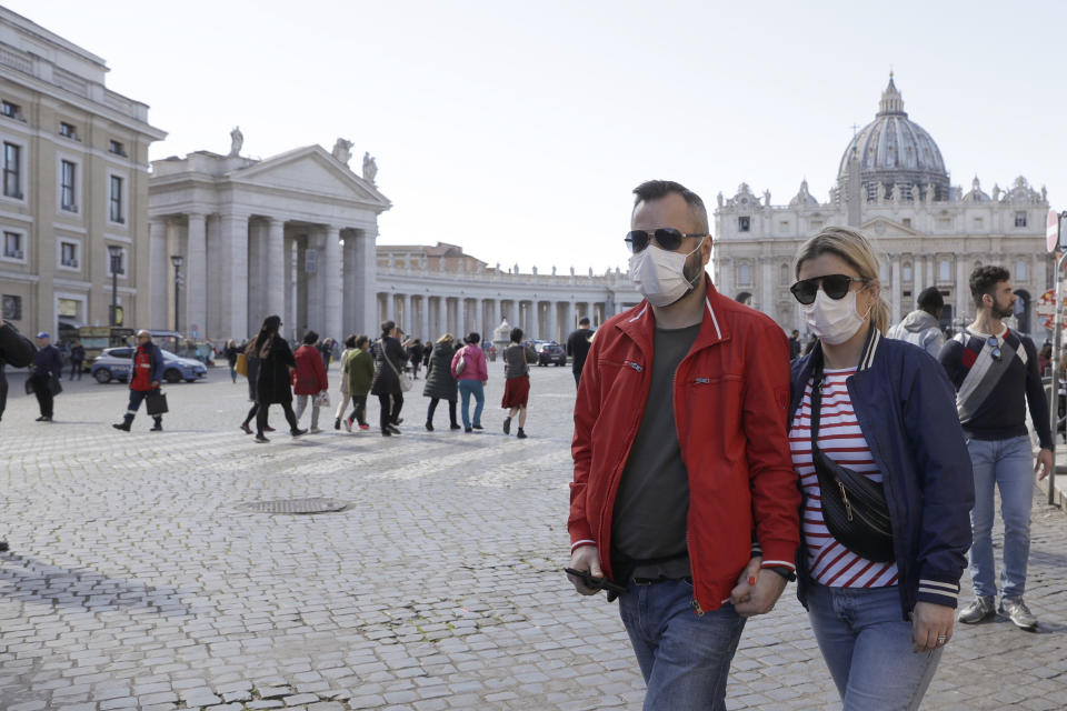 A couple wearing face masks, stroll outside St. Peter's Square, at the Vatican, Thursday, Feb. 27, 2020. In Europe, an expanding cluster in northern Italy is eyed as a source for transmissions of the COVID-19 disease (AP Photo/Gregorio Borgia)