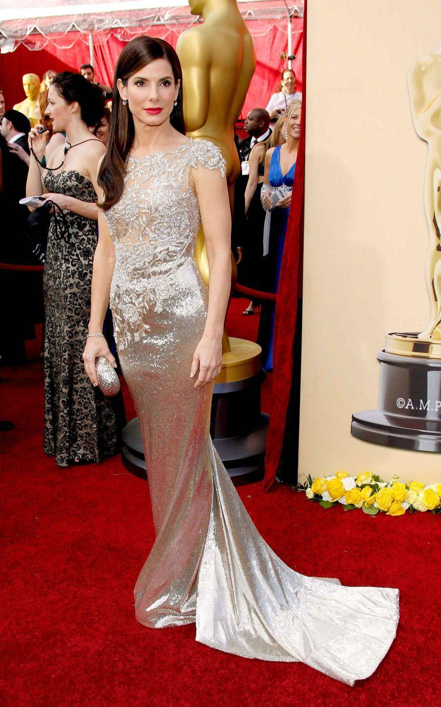 <p>Sandra Bullock in a champagne Marchesa dress with lace details.</p>