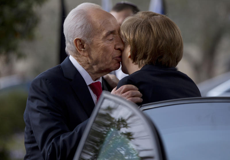 FILE - In this file photo taken Tuesday, Feb. 25, 2014, Israel's President Shimon Peres kisses German Chancellor Angela Merkel as she arrives to receive the Presidential Medal ceremony at the President's residence in Jerusalem. Among those vying to become Israel's next president are a former defense minister, a former foreign minister, a former finance minister, a respected long-serving lawmaker and a Nobel Prize winner. Amazingly, the man they all seek to replace has held all of those titles and more during a legendary 65-year political career. (AP Photo/Ariel Schalit, File)