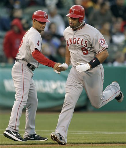 Los Angeles Angels' Albert Pujols, right, is congratulated by third base coach Dino Ebel after hitting a home run off Oakland Athletics' Graham Godfrey in the third inning of a baseball game, Tuesday, May 22, 2012, in Oakland, Calif. (AP Photo/Ben Margot)