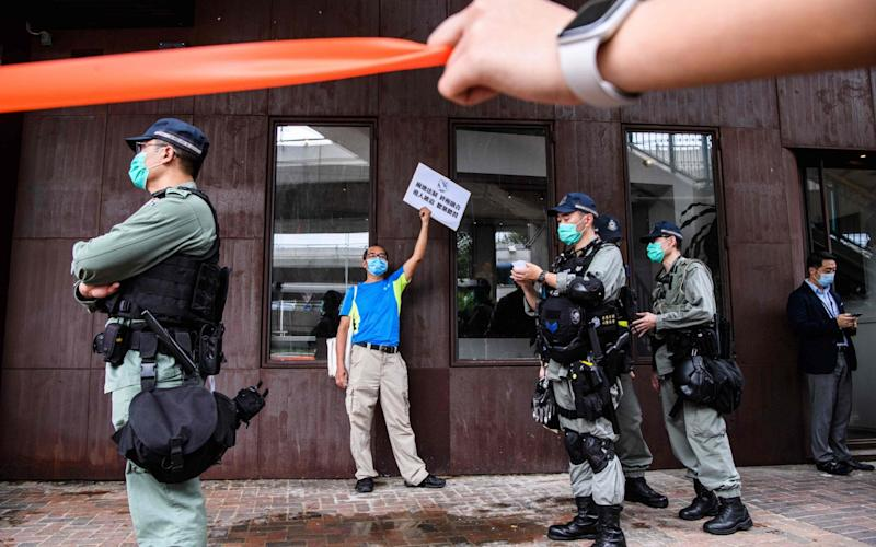 Riot police stand guard near a pro-democracy protester, who was stopped with others before being fined for breaking government-imposed social distancing rules - ANTHONY WALLACE/AFP