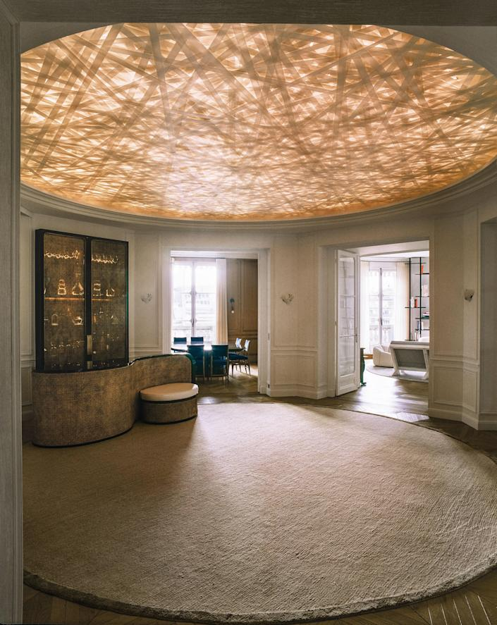 Stanislas-designed bar sits on a bespoke silk rug by J.D. Staron in the circular entrance hall. The ceiling installation was created by artist Yann Kersalé.