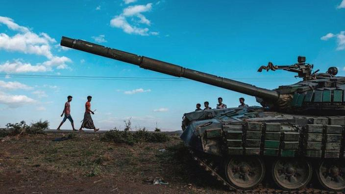 Young people walk next to an abandoned tank belonging to Tigrayan forces south of the town of Mehoni, Ethiopia - 11 December 2020