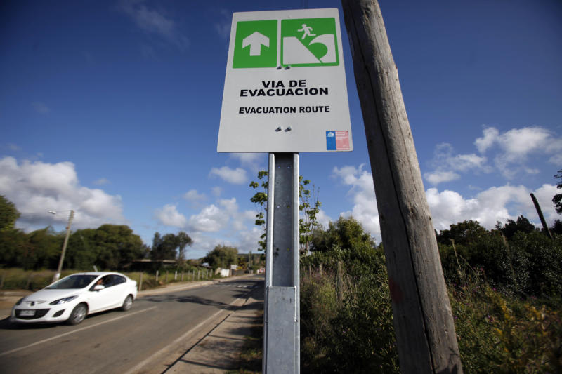 FILE - In this Nov. 29, 2012, file photo, a car drives by a sign indicating the evacuation route in the event of a tsunami, in Navidad, Chile. A strong magnitude-6.7 earthquake off Chile's far-northern coast on March 16. 2014, caused more than 100,000 people to briefly evacuate low-lying areas and has been followed by an unsettling string of more than 300 aftershocks. Chile is one of the world's most earthquake-prone countries. (AP Photo/Luis Hidalgo, File)