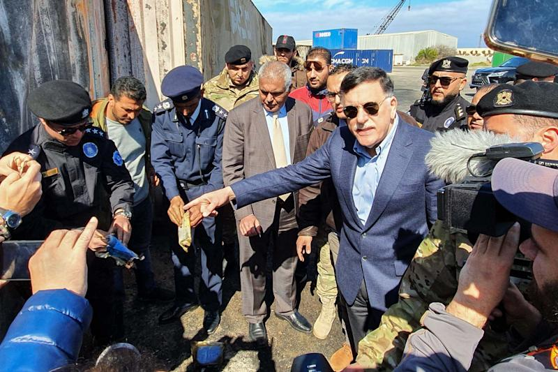Prime Minister of Libya's UN-recognised Government of National Accord (GNA) Fayez al-Sarraj, flanked by journalists, visits the port in the capital Tripoli after it was hit by rocket fire: AFP via Getty Images