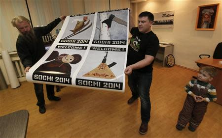 """Russian artist Vasily Slonov (L) and an employee carry printed reproductions of oil paintings from the series """"Welcome Sochi 2014"""" at a printing house in Russia's Siberian city of Krasnoyarsk, December 9, 2013. REUTERS/Ilya Naymushin"""