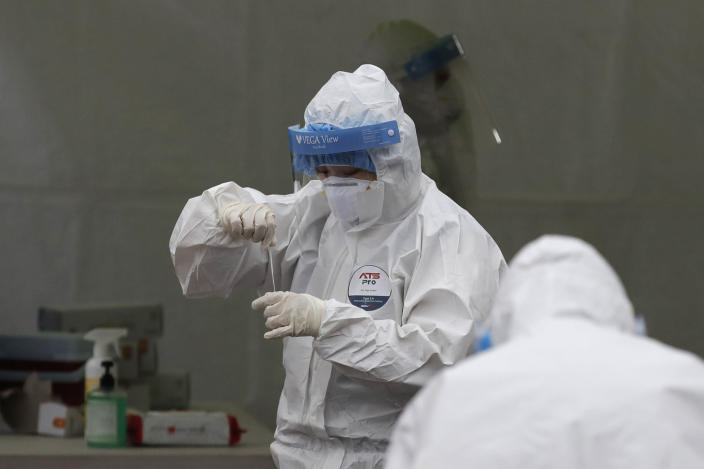 Medical workers wearing protective gears work at a coronavirus testing site in Seoul, South Korea, Wednesday, Dec. 23, 2020. South Korea has added more than 1,000 new coronavirus cases in a resurgence that is erasing hard-won epidemiological gains and eroding public confidence in the government's ability to handle the outbreak. (AP Photo/Lee Jin-man)
