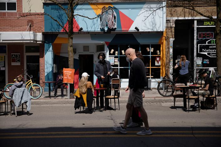 People walk as outdoor dining crowds outside of restaurants as coronavirus disease (COVID-19) restrictions are eased in Ann Arbor, Michigan, U.S., April 4, 2021.  REUTERS/Emily Elconin