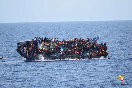 "Migrants are seen on a capsizing boat before a rescue operation by Italian navy ships ""Bettica"" and ""Bergamini"" (unseen) off the coast of Libya in this handout picture released by the Italian Marina Militare on May 25, 2016. Marina Militare/Handout via REUTERS"