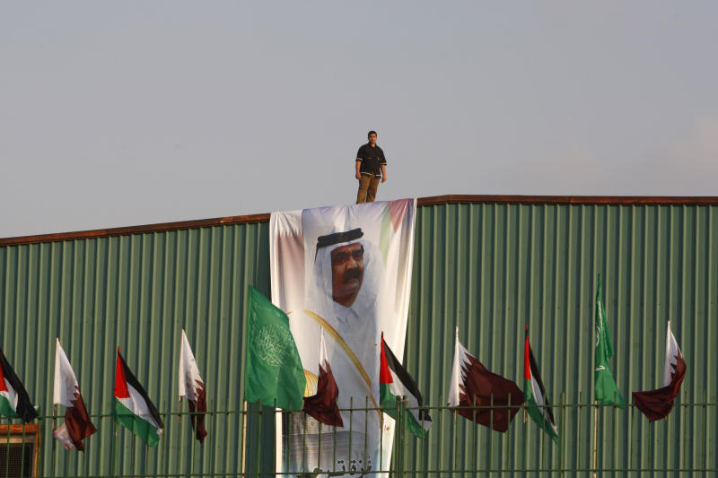 A Palestinian worker stands above a poster of the Emir of Qatar Sheikh Hamad bin Khalifa al-Thani, while bellow are flags of Qatar, Islamic green of Hamas and Palestinian flags in preparation for the upcoming visit to Gaza at Palestine stadium in Gaza City, Monday, Oct. 22, 2012. (AP Photo/Adel Hana)