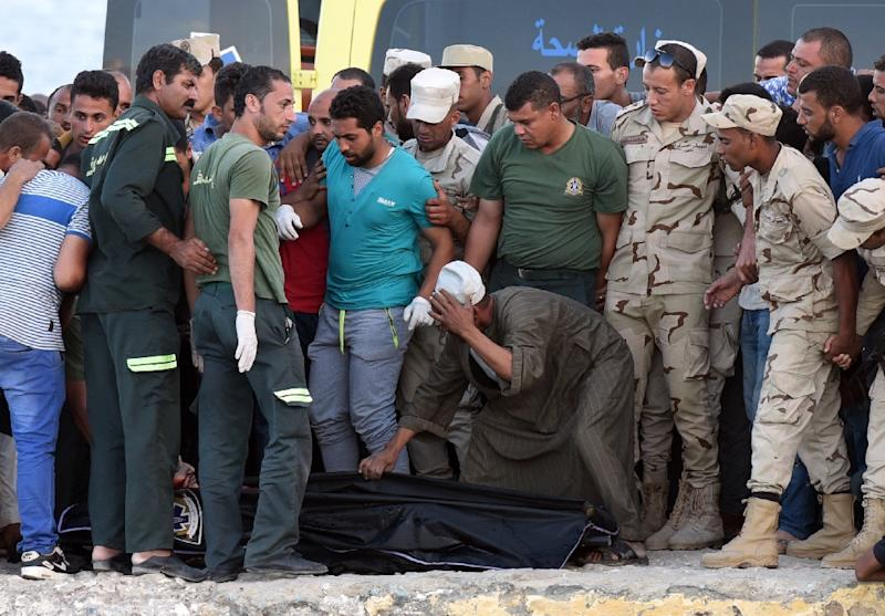 Policemen and medics gather around the body of a migrant along the shore in the Egyptian port city of Rosetta on September 22, 2016, during a search operation after a boat capsized in the Mediterranean (AFP Photo/Mohamed El-Shahed)