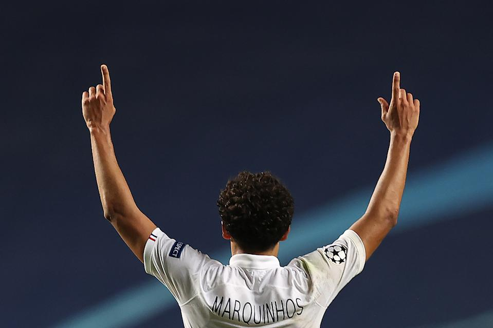 Marquinhos raises his arms in celebration. The photo is taken from behind him.