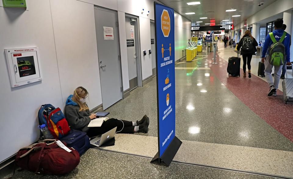A Bowdoin College student sits on the floor doing her homework on her way home to Portland Oregon in a social distancing atmosphere at Terminal B at Boston Logan International Airport on Nov. 23, 2020. (David L. Ryan/The Boston Globe via Getty Images)