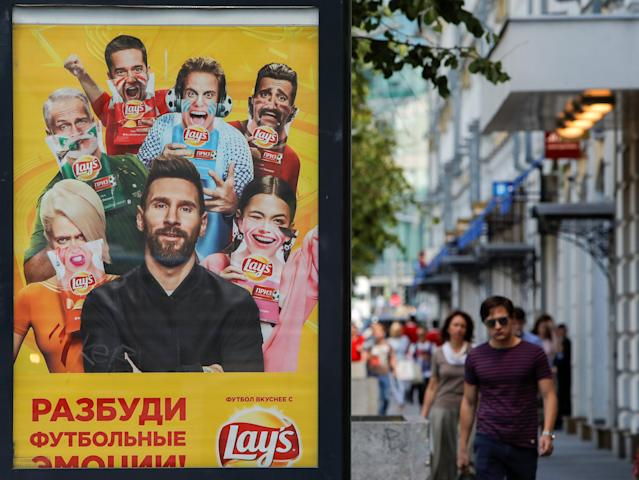 People walk past an advertisement poster depicting Argentina's soccer player Lionel Messi in Moscow, Russia June 20, 2018. Picture taken June 20, 2018. REUTERS/Sergei Karpukhin