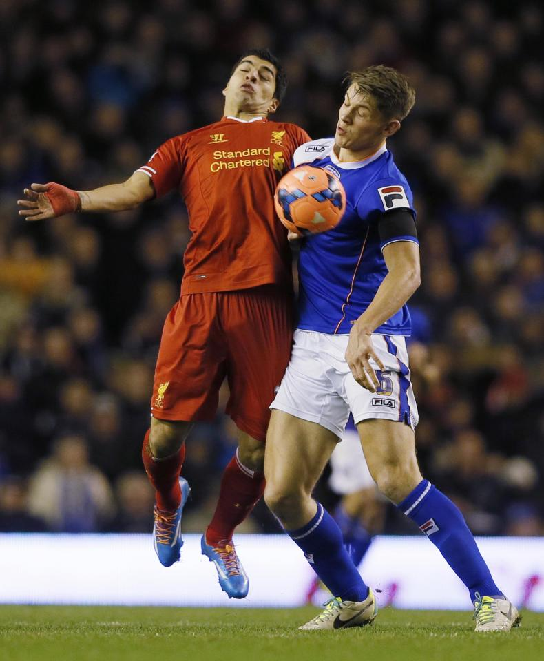 Liverpool's Luis Suarez challenges Oldham Athletic's James Tarkowski during their FA Cup third round soccer match at Anfield in Liverpool January 5, 2014. REUTERS/Phil Noble (BRITAIN - Tags: SPORT SOCCER)
