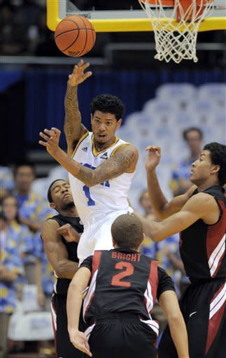 UCLA guard Tyler Lamb, top, passes the ball as Stanford guard Chasson Randle, rear guard Aaron Bright, front, and forward Josh Huestis defend during the first half of an NCAA college basketball game, Thursday, Feb. 9, 2012, in Los Angeles. (AP Photo/Mark J. Terrill)