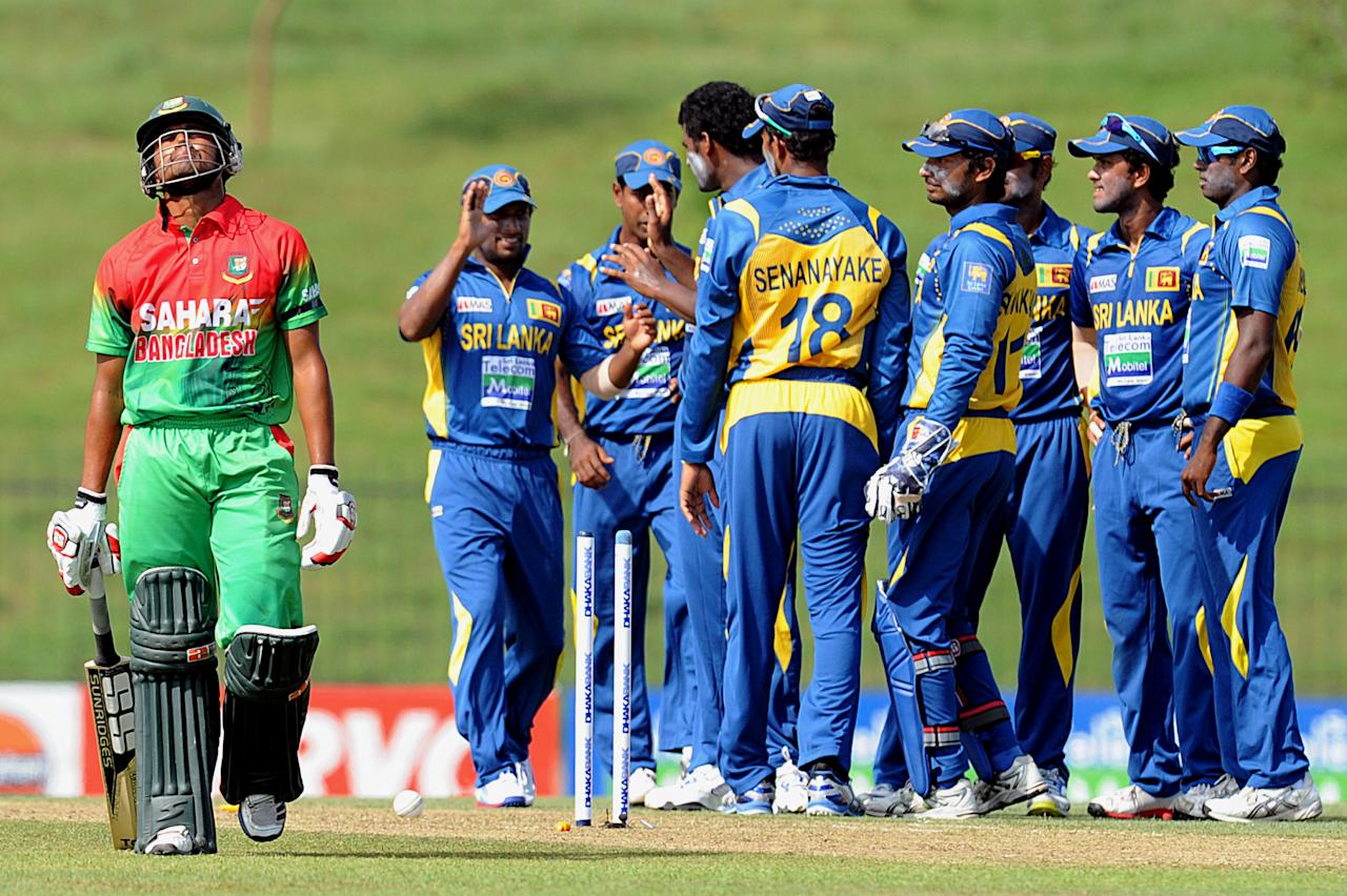 Bangladeshi cricketer Anamul Haque (L) leaves the field as Sri Lankan cricketer Thisara Perera (4L) celebrates with teammates during the opening one-day international (ODI) match between Sri Lanka and Bangladesh at The Suriyawewa Mahinda Rajapakse International Cricket Stadium in the southern district of Hambantota on March 23, 2013. Sri Lankan cricket captain Angelo Mathews won the toss and elected to field. AFP PHOTO/ Ishara S. KODIKARA (Photo credit should read Ishara S.KODIKARA/AFP/Getty Images)