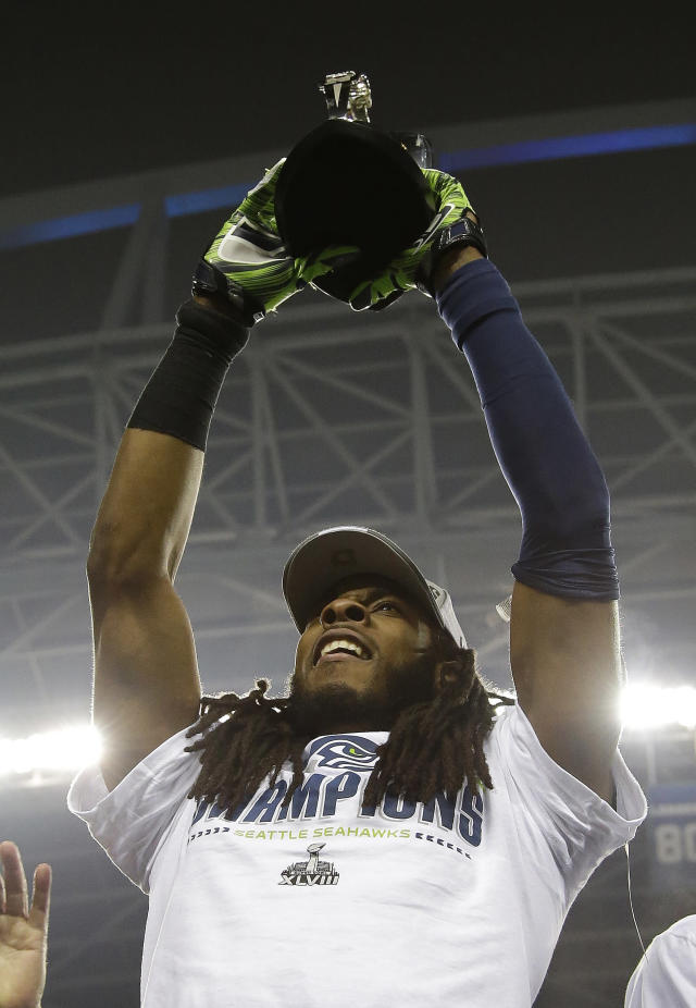 Seattle Seahawks' Richard Sherman holds up the George Halas Trophy after the NFL football NFC Championship game against the San Francisco 49ers Sunday, Jan. 19, 2014, in Seattle. The Seahawks won 23-17 to advance to Super Bowl XLVIII. (AP Photo/Matt Slocum)
