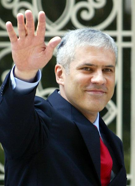 FILE - July 11, 2004 file photo of Serbia's first democratic president Boris Tadic, as he waves to supporters after taking his oath of office in the parliament building and stepping into the Serbian presidency building for an inauguration ceremony, in Belgrade, Serbia. Tadic said Wednesday April 4 2011 that he is resigning, paving the way for an early presidential election where he will face a strong challenge from a nationalist candidate. In the presidential vote, Tadic will be challenged by nationalist candidate Tomislav Nikolic who has received tacit support from Russia. (AP Photo/Darko Vojinovic, file)