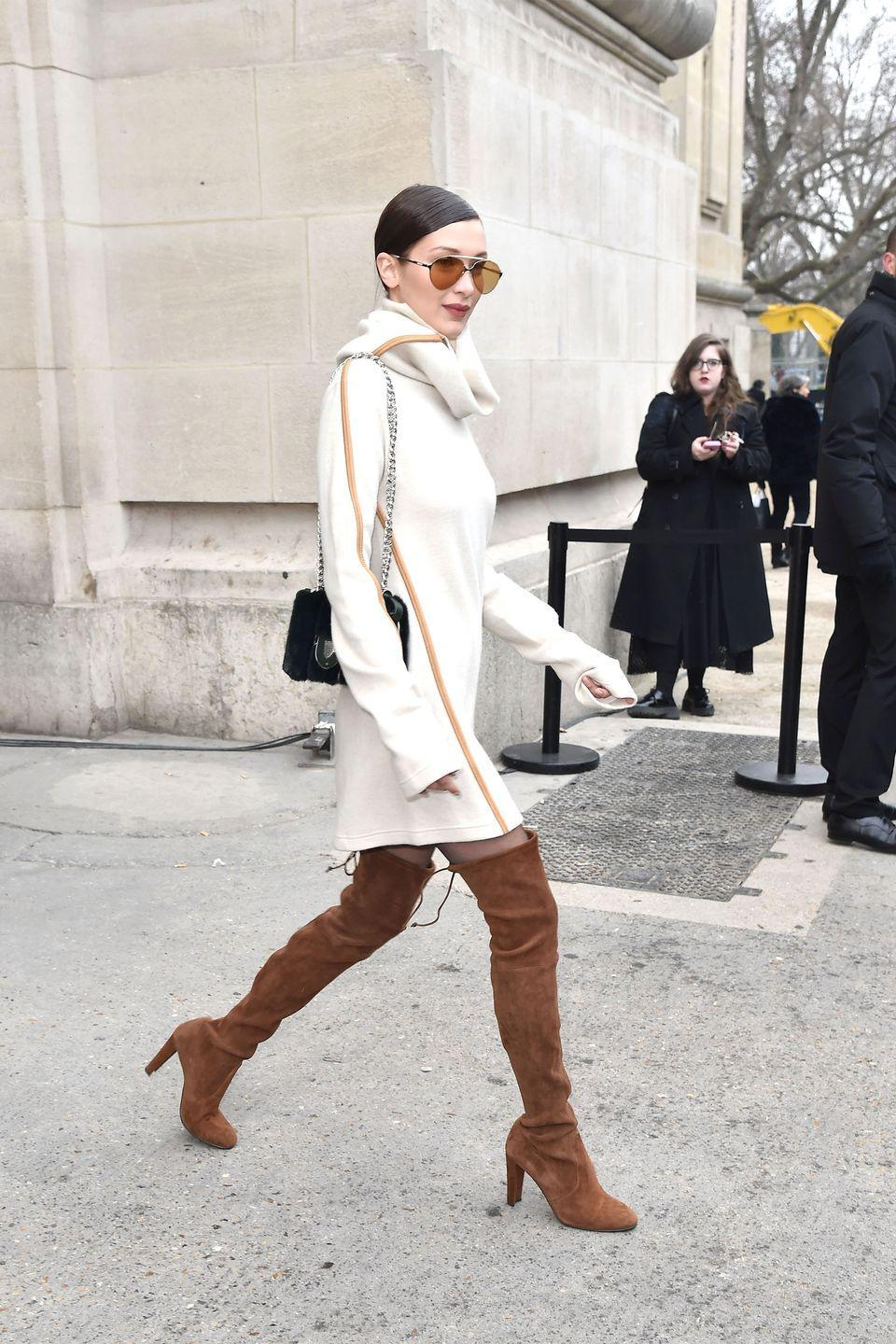 <p>In a Céline cream cowl neck sweater dress, Stuart Weitzman suede over-the-knee boots, Carrera aviator sunglasses and fur bag while leaving the Chanel couture show in Paris.</p>