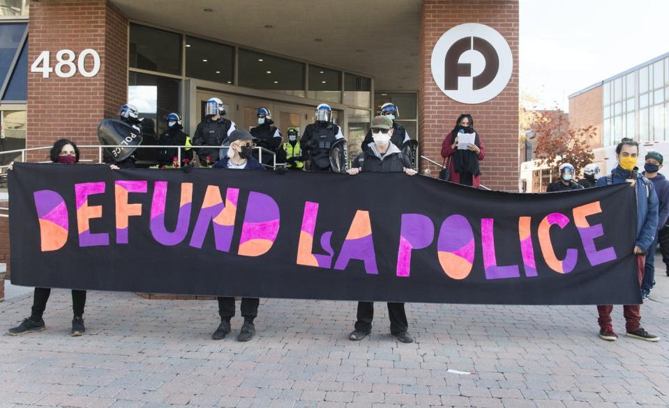 Protesters hold up a sign that says Defund La Police.