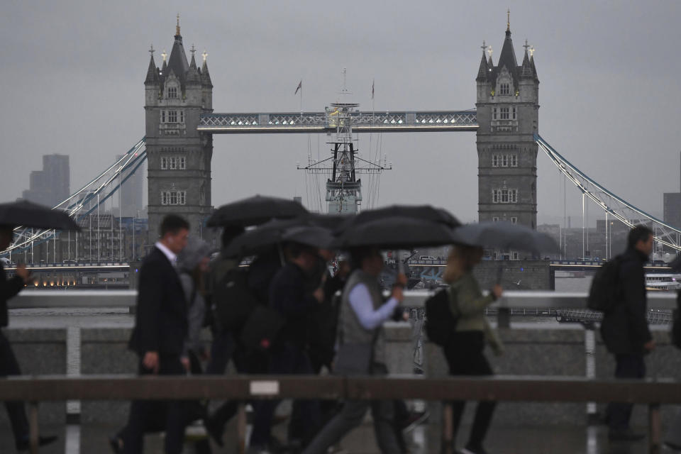 Commuters cross London Bridge, with Tower Bridge in the background, as parts of Britain brace for continuing bad weather, as light fades in London, Monday Sept. 30, 2019.  Two more days of heavy downpours are predicted for later this week.  (Kirsty O'Connor/PA via AP)