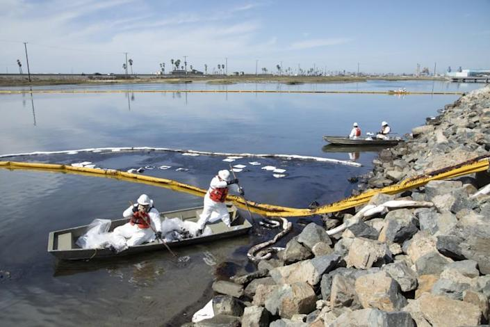 Workers with Patriot Environmental Services clean up oil that flowed into the Talbert Marsh in Huntington Beach.