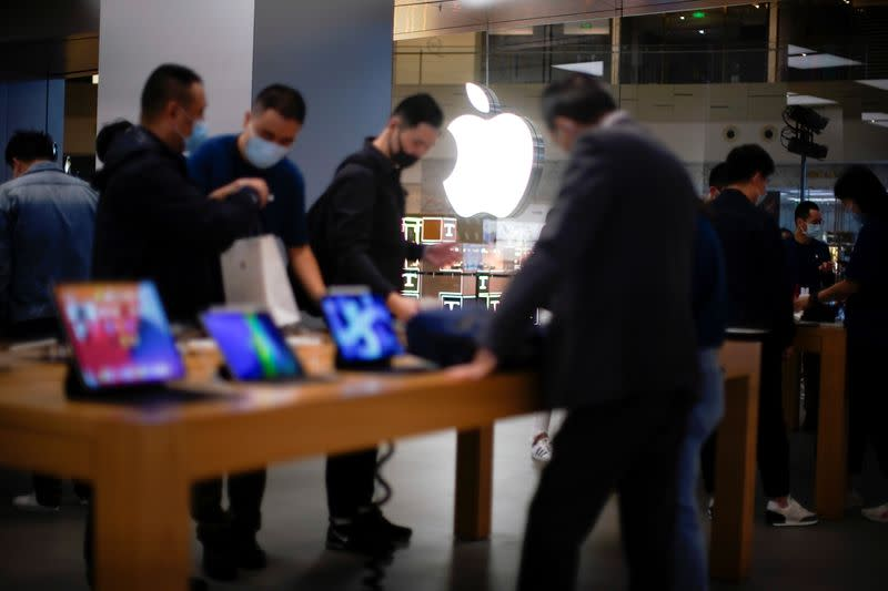 People look at Apple products at an Apple Store, as the coronavirus disease (COVID-19) outbreak continues in Shanghai