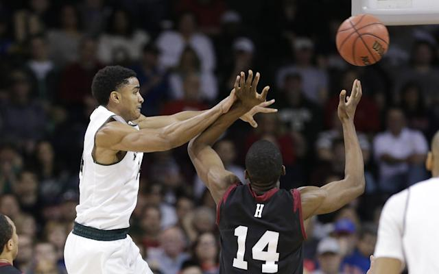 Michigan State's Gary Harris, left, passes as Harvard's Steve Moundou-Missi (14) defends in the first half during the third round of the NCAA men's college basketball tournament in Spokane, Wash., Saturday, March 22, 2014. (AP Photo/Elaine Thompson)