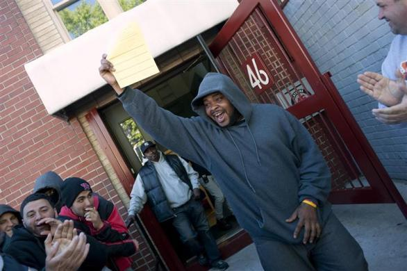 Job seeker Matthew Cox, the first person in line, cheers after picking up a job application form at the training offices of Local Union 46, a union representing metallic lathers and reinforcing ironworkers, in the Queens borough of New York, April 30, 2012.