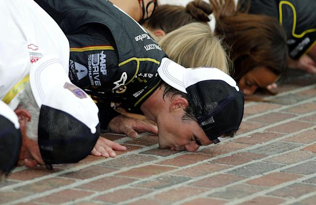 Jeff Gordon celebrates by kissing the bricks after winning the NASCAR Brickyard 400 auto race at Indianapolis Motor Speedway in Indianapolis, Sunday, July 27, 2014. (AP Photo/Robert Baker)