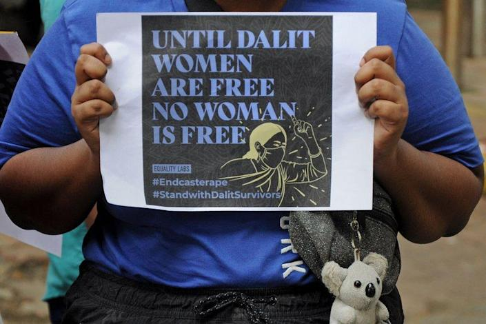 A protester holds a placard during a demonstration against caste-based sexual violence.