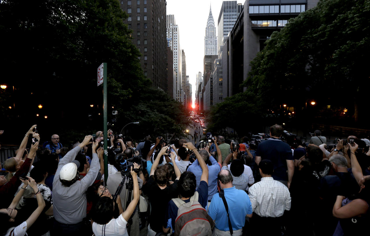 Photographers aim their cameras as the sun sets through the buildings on 42nd Street in New York's Manhattan borough during a phenomenon known as Manhattanhenge, Wednesday, July 11, 2012. Manhattanhenge, sometimes referred to as the Manhattan Solstice, happens when the setting sun aligns with the east-to-west streets of the main street grid. The term references Stonehenge, at which the sun aligns with the stones on the solstices in England. (AP Photo/Julio Cortez)