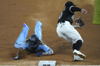 Toronto Blue Jays' Vladimir Guerrero Jr., left, arrives safely at third against Chicago White Sox third baseman Yoan Moncada during the sixth inning of a baseball game in Chicago, Thursday, June 10, 2021. Wild pitch by Chicago White Sox starting pitcher Dallas Keuchel. (AP Photo/Nam Y. Huh)