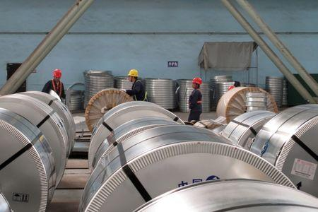 Workers pack cold rolled steel coil at a steel company in Zhangjiagang