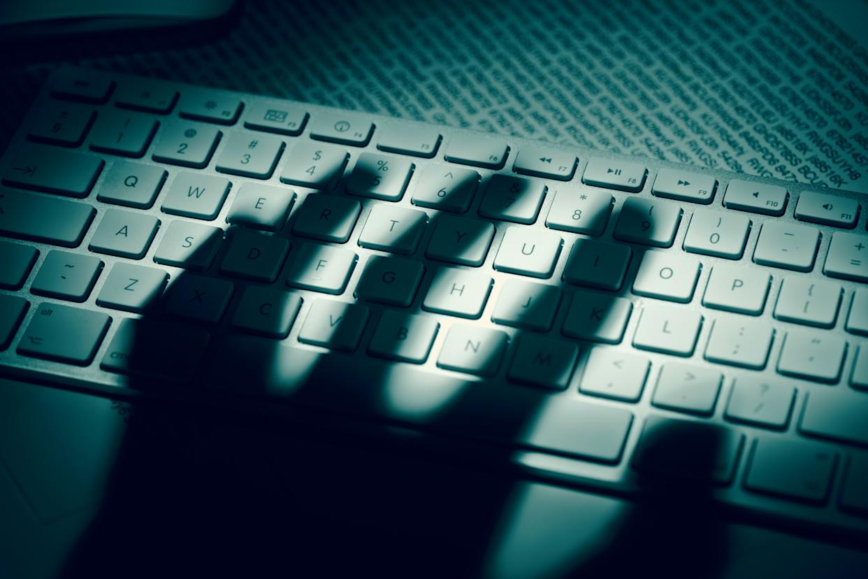 The shadow of an anonymous person's hand hovers over a computer keyboard. (Image:&nbsp; <span>Dimitris66 via Getty Images)</span>