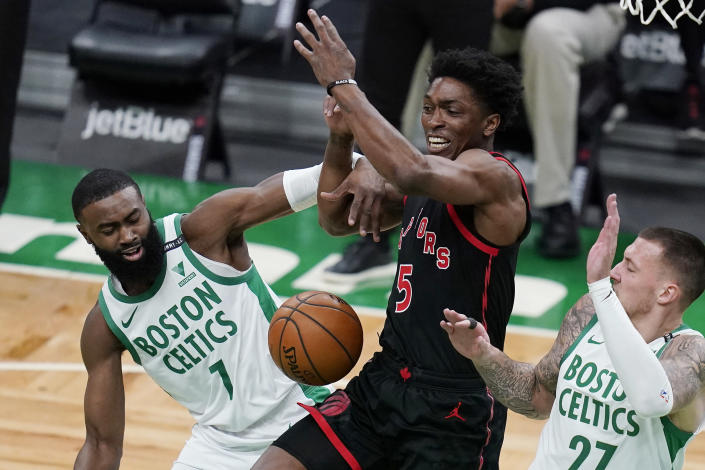 Boston Celtics guard Jaylen Brown (7) fouls Toronto Raptors forward Stanley Johnson (5) during the first half of an NBA basketball game, Thursday, March 4, 2021, in Boston. At right is Boston Celtics center Daniel Theis. (AP Photo/Charles Krupa)
