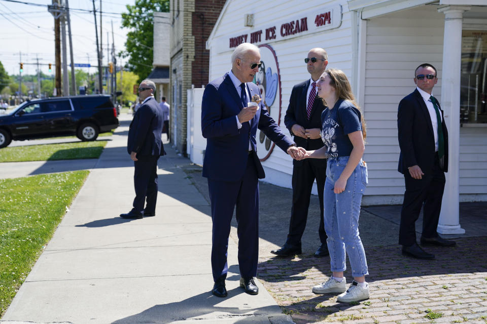 President Joe Biden talks with an employee as he holds an ice cream cone at Honey Hut Ice Cream, Thursday, May 27, 2021, in Cleveland. (AP Photo/Evan Vucci)