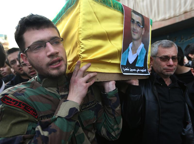 The father, right, and brother of Ali Khadra, left, who was killed Thursday by a bomb explosion, carry his coffin during his funeral procession in the southern suburb of Beirut, Lebanon, Saturday, Jan. 4, 2014. An explosion tore through a crowded commercial street Thursday in a south Beirut neighborhood that is bastion of support for the Shiite group Hezbollah, killing several people, setting cars ablaze and sending a column of black smoke above the Beirut skyline. (AP Photo/Hussein Malla)