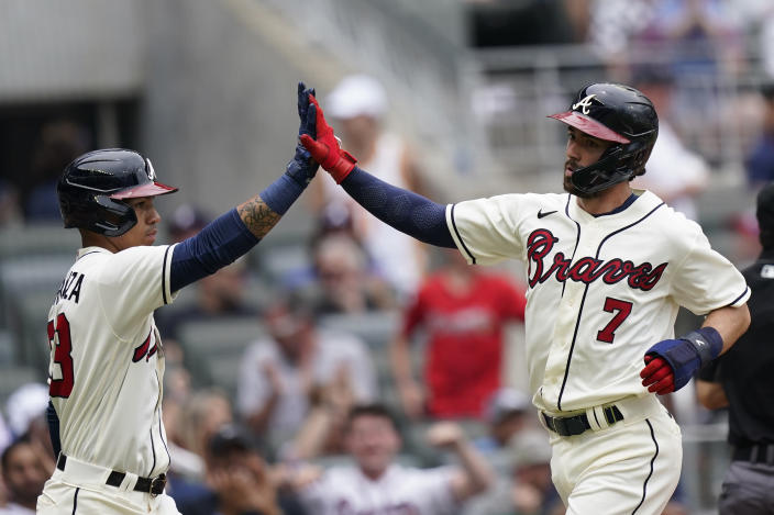 Atlanta Braves' Dansby Swanson, right, celebrates with Ehire Adrianza, left, after scoring in the second inning of a baseball game against the Los Angeles Dodgers Sunday, June 6, 2021, in Atlanta. (AP Photo/Brynn Anderson)