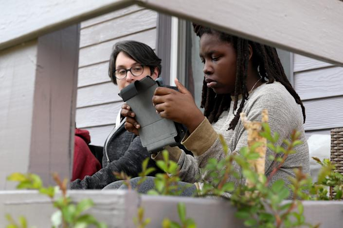 Rose Curtin, left, looks over Haddasha Revely-Curtin's shoulder while she does school work, Thursday, April 2, 2020, in Newport, Ky. Haddasha, 12, is a sixth-grade student at Newport Intermediate School.