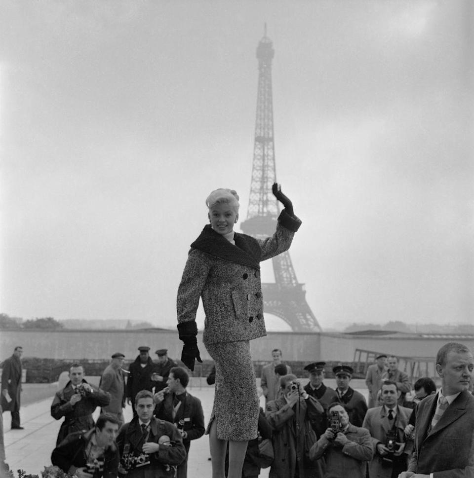 <p>The blonde beauty waves to the paparazzi at the Trocadéro, with the Eiffel Tower in the distance. Purely picturesque!</p>
