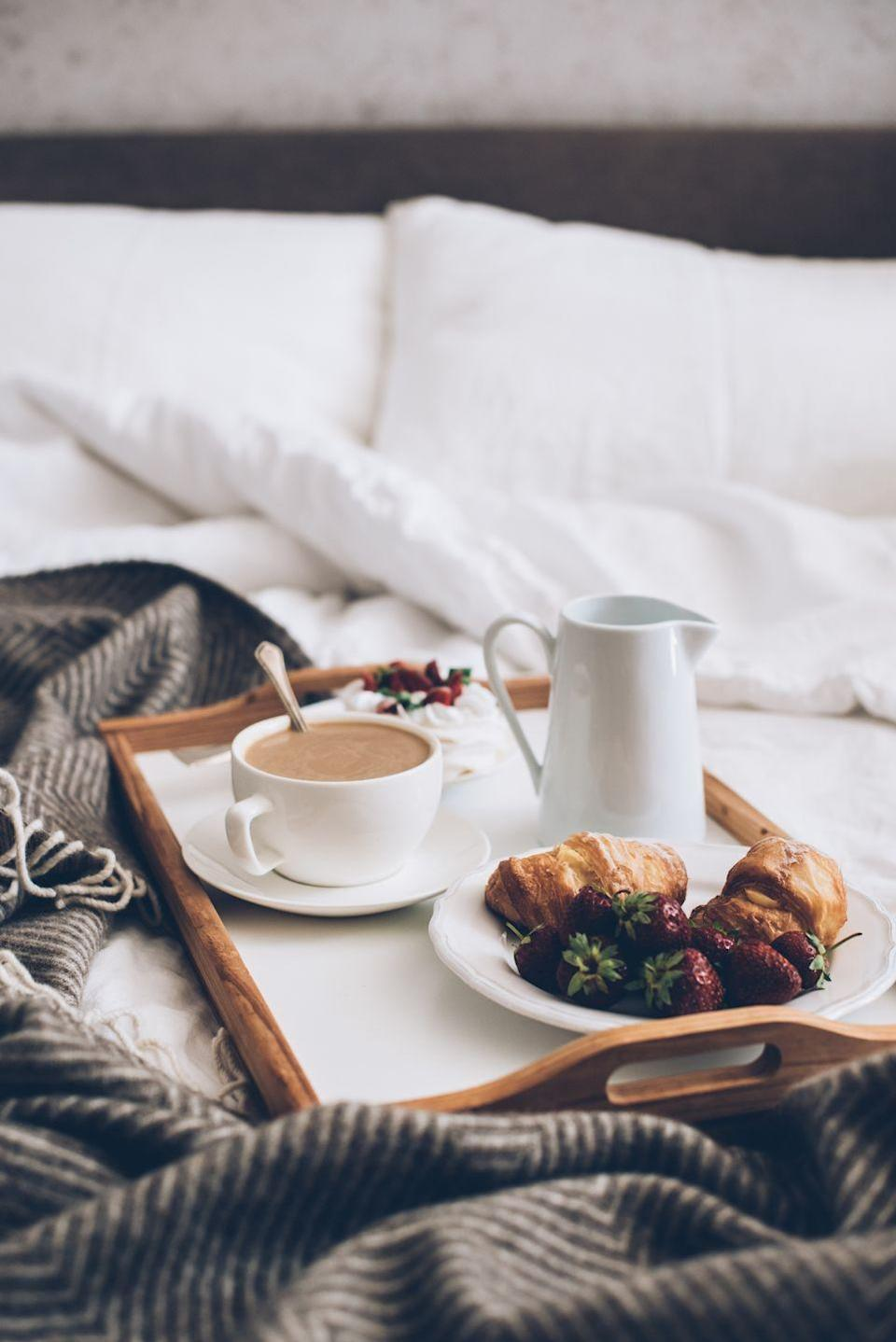 """<p>Simple gestures like breakfast in bed become special when you take them to the next level. Make a huge spread of their favorite things on a <a href=""""https://www.urbanoutfitters.com/shop/laurie-bed-tray"""" rel=""""nofollow noopener"""" target=""""_blank"""" data-ylk=""""slk:cute tray"""" class=""""link rapid-noclick-resp"""">cute tray</a>—bonus points if things like pancakes or waffles are heart-shaped and serve with a favorite book, newspaper or magazine. If cooking isn't your strong suit, then order <a href=""""https://www.williams-sonoma.com/products/williams-sonoma-ready-to-bake-chocolate-croissants/?catalogId=79&sku=2683453&cm_ven=PLA&cm_cat=Google&cm_pla=Food%20%3E%20Croissants%20%26%20Pastries%C2%AEion_id=669950&cm_ite=2683453&gclid=CjwKCAiArIH_BRB2EiwALfbH1MneHSW1cbEqWVJAv_uJBfqDOxAbRzinhvh1XZcjuQDtfNjmNIAEKhoCbl8QAvD_BwE"""" rel=""""nofollow noopener"""" target=""""_blank"""" data-ylk=""""slk:these chocolate croissants"""" class=""""link rapid-noclick-resp"""">these chocolate croissants</a> to serve gooey out of the oven and pick up their favorite coffee. </p>"""