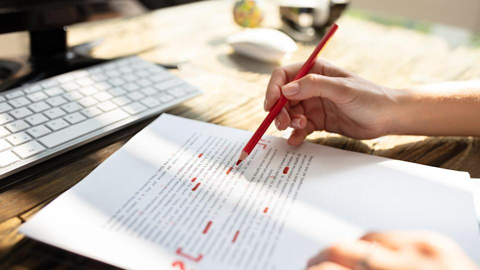 Close-up Of A Person's Hand Marking Error With Red Marker On Document.