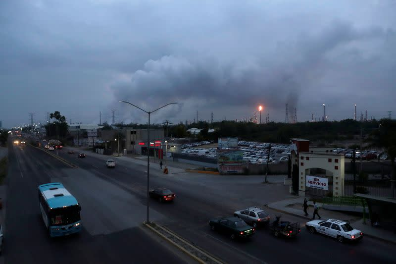 Excess natural gas is burnt, or flared, in the distance from Mexican state-run Pemex's Tula oil refinery as seen from a pedestrian bridge next to the Tula power plant belonging to national power company Commission Federal de Electricidad