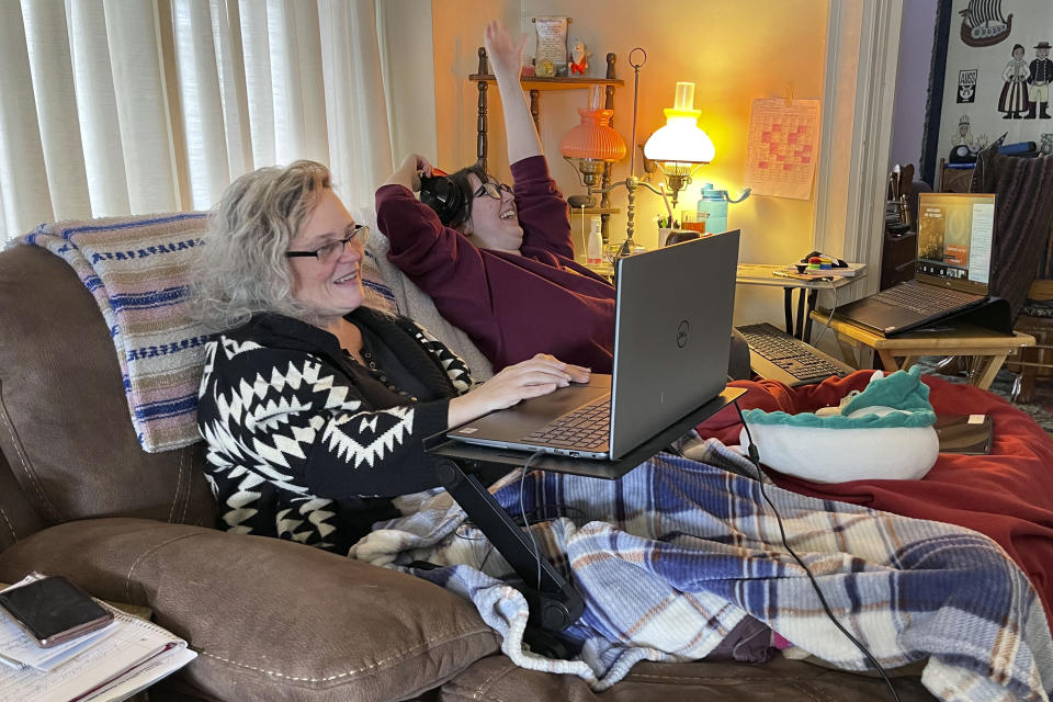 Angelina Mistretta, a 16-year-old junior at City Honors High School shares the couch with her mother Wendy Mistretta, in Buffalo, NY., Feb. 17, 2021. These days, her mother, Wendy, works beside Angelina on the living room couch. (AP Photo/Carolyn Thompson)
